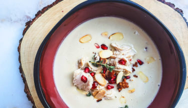 turkey cream soup with bacon, pine nuts, and pomegranate garnish